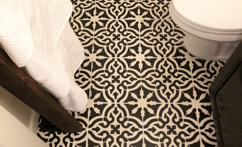 Stenciled cermaic tiles in bathroom, done in Blackberry House paint- black and white tile floors